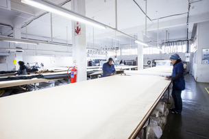Male and female factory workers marking textile in clothing factoryの写真素材 [FYI03578211]