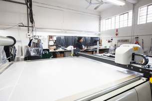 Pattern cutting machine and factory worker in clothing factoryの写真素材 [FYI03578214]