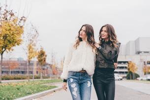 Twin sisters walking outdoors, looking awayの写真素材 [FYI03578249]