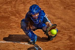 Teenage girl catching baseballの写真素材 [FYI03578308]