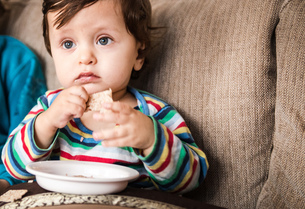 Baby boy sitting on sofa watching TV while eating a snackの写真素材 [FYI03578511]