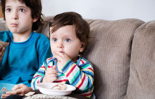 Baby boy and big brother sitting on sofa watching TV while eating a snackの写真素材 [FYI03578513]