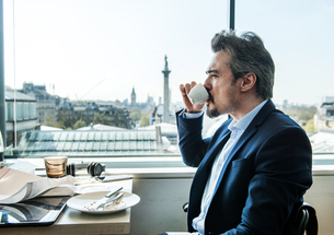 Businessman drinking coffee by restaurant window with rooftops views, London, UKの写真素材 [FYI03578544]