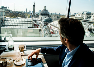 Businessman using digital tablet by restaurant window with rooftop views, London, UKの写真素材 [FYI03578555]