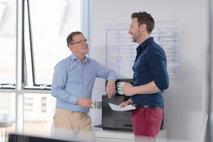 Male colleagues talking by photocopier machineの写真素材 [FYI03578569]
