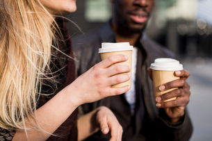 Cropped shot of young couple holding takeaway coffee in cityの写真素材 [FYI03578740]