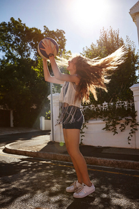 Teenage girl catching ball in street, Cape Town, South Africaの写真素材 [FYI03578766]