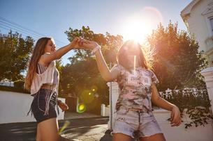 Teenage girls having fun in residential street, Cape Town, South Africaの写真素材 [FYI03578774]