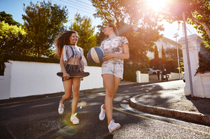 Teenage girls with ball and skateboard in street, Cape Town, South Africaの写真素材 [FYI03578780]