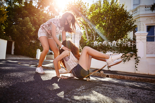 Teenage girl catching friend falling off skateboard, Cape Town, South Africaの写真素材 [FYI03578781]