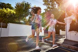 Teenage girls having fun in residential street, Cape Town, South Africaの写真素材 [FYI03578783]