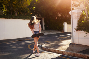 Teenage girl with skateboard in street, Cape Town, South Africaの写真素材 [FYI03578796]