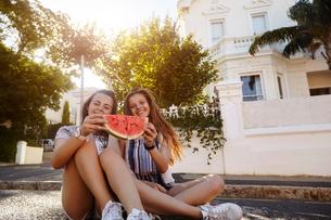 Teenage girls having watermelon in street, Cape Town, South Africaの写真素材 [FYI03578800]