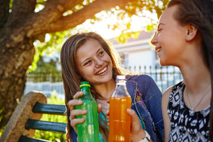 Two female friends sitting outdoors, holding soft drinks, smilingの写真素材 [FYI03578837]