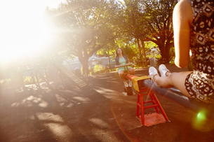 Two female friends at park, fooling around on see-sawの写真素材 [FYI03578849]