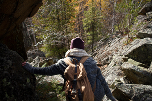 Young woman hiking, leaning on rock, rear view, Sverdlovsk Oblast, Russiaの写真素材 [FYI03578860]
