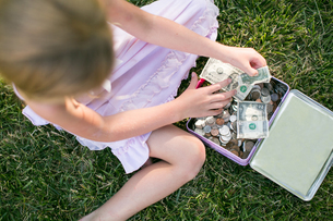 Overhead view of girl counting dollar bills on grassの写真素材 [FYI03579046]