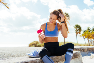 Young female runner sitting with takeaway drink on beach wallの写真素材 [FYI03579055]