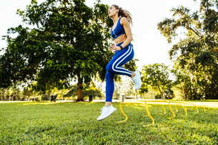 Young woman training, jumping agility hurdles in parkの写真素材 [FYI03579073]