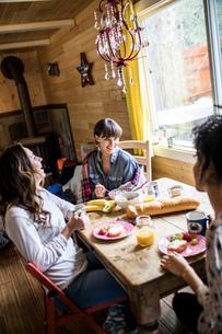 Three friends sitting around table, eating breakfastの写真素材 [FYI03579095]