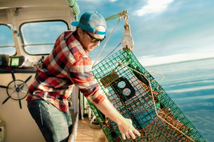 Young man lifting lobster cage from winch on fishing boat on coast of Maine, USAの写真素材 [FYI03579160]