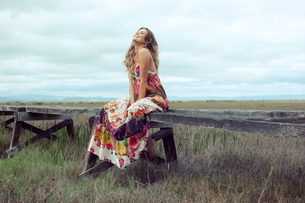 Young woman in boho maxi dress sitting on elevated wooden walkway in landscapeの写真素材 [FYI03579254]