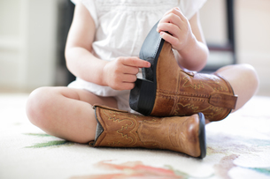 Neck down view of female toddler sitting on floor wearing cowboy bootsの写真素材 [FYI03579287]