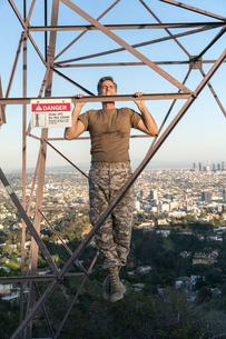 Soldier wearing combat clothing doing chin ups on electricity pylon, Runyon Canyon, Los Angeles, Calの写真素材 [FYI03579438]