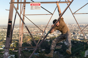 Soldier wearing combat clothing dangling from electricity pylon, Runyon Canyon, Los Angeles, Califorの写真素材 [FYI03579439]
