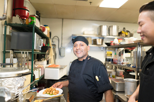 Chef in commercial kitchen smiling at cameraの写真素材 [FYI03579451]