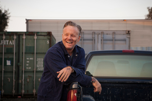 Man leaning against truck smilingの写真素材 [FYI03579495]