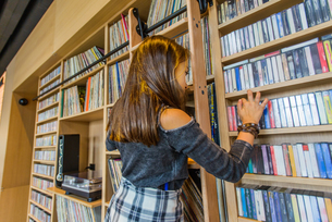 Girl searching cassette tapes on shelfの写真素材 [FYI03579578]