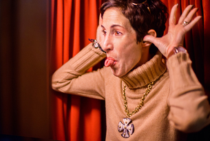 Woman sticking out tongue, red curtain backgroundの写真素材 [FYI03579589]