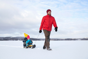 Father pulling sons along on sledge in snow covered landscapeの写真素材 [FYI03579738]