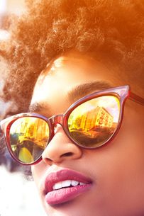 Close up portrait of young female fashion blogger with afro hair and mirrored sunglasses, New York,の写真素材 [FYI03579868]