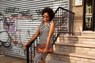 Young female fashion blogger with afro hair on urban stairs, New York, USAの写真素材 [FYI03579872]