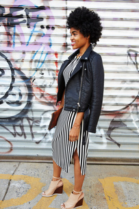 Young female fashion blogger with afro hair by graffiti wall, New York, USAの写真素材 [FYI03579875]