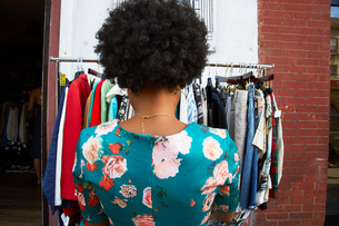 Rear view of young female fashion blogger with afro hair looking at vintage clothes rail, New York,の写真素材 [FYI03579876]
