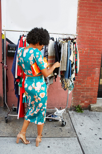 Rear view of young female fashion blogger with afro hair looking at sidewalk clothes rail, New York,の写真素材 [FYI03579877]
