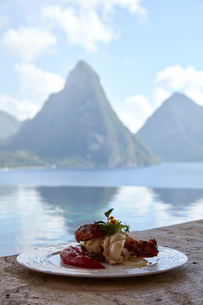 Fresh local lobster dish with view of the Pitons, Saint Lucia, Caribbeanの写真素材 [FYI03579894]