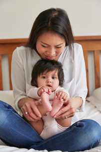Portrait of woman cross legged on bed with baby daughterの写真素材 [FYI03580037]