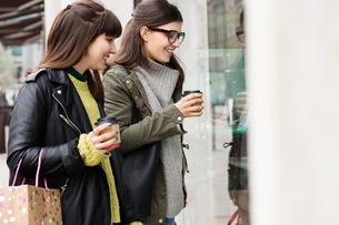 Two young female shoppers with takeaway coffee looking in shop windowの写真素材 [FYI03580093]
