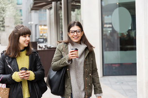 Two young women chatting while strolling on street  with takeaway coffeeの写真素材 [FYI03580094]