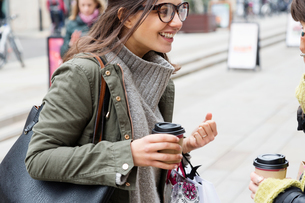 Two young female shoppers with takeaway coffee chatting on streetの写真素材 [FYI03580096]