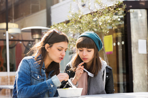 Two young women eating takeaway food at market picnic benchの写真素材 [FYI03580116]