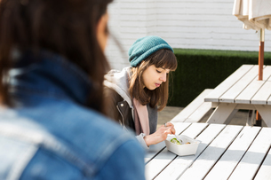 Young women eating takeaway food at picnic benchの写真素材 [FYI03580118]