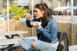 Young women eating takeaway food on picnic benchの写真素材 [FYI03580119]
