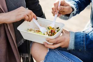 Hands of young women sharing takeaway foodの写真素材 [FYI03580121]
