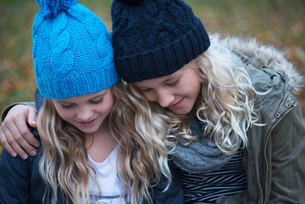 Blond haired sisters wearing knit hats looking down in gardenの写真素材 [FYI03580196]