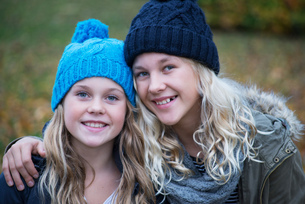 Portrait of blond haired sisters wearing knit hats in gardenの写真素材 [FYI03580197]